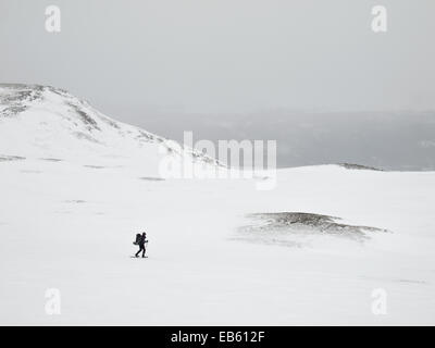 man  with heavy pack viewed from a distance snowshoeing through a winter mountain landscape - Stock Image