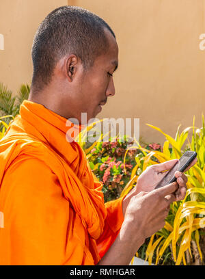 Buddhist Monk in a saffron (orange ) robe  checking his mobile phone  for messages in the grounds of  The Royal Palace, in Phnom Penh, Cambodia - Stock Image
