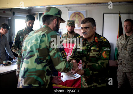 HELMAND PROVINCE, Afghanistan (August 26, 2018) – Afghan Brig. Gen. Abdul Hadi, Afghan National Army (ANA) 215th Corps deputy commander, hands an ANA soldier his certificate of completion during a graduation ceremony for a train-the-trainer course at the Regional Military Training Center on Camp Shorabak. The nearly month-long course taught instructors the basics of warrior training so they can, in turn, teach the upcoming classes of the new ANA Territorial Force who will assist in providing safe and secure elections to the people of Helmand and provinces this October. (U.S. Marine Corps photo - Stock Image