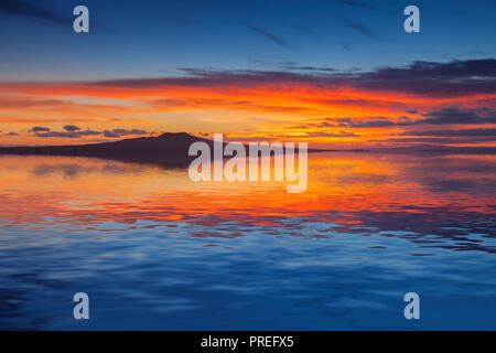 Rangitoto Island at sunrise, Auckland, New Zealand, reflected in the waters of the Hauraki Gulf. - Stock Image
