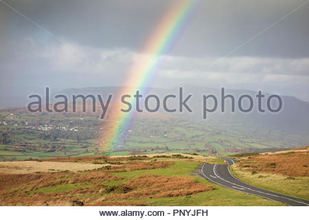 Rainbow in a autumn rural landscape by mountain road, Mynydd Llangynidr, Brecon Beacons National Park; Black Mountains in distance; Powys, Wales, UK. - Stock Image