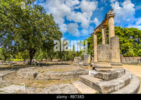 Tourists visit the ancient Philippeion in the Altis of Olympia, an Ionic circular memorial in limestone and marble in Olypia, Greece. - Stock Image