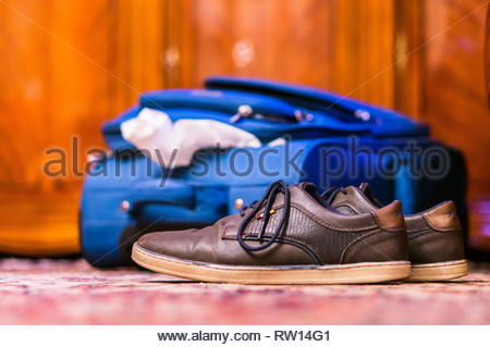 Rotterdam, The Netherlands - February 18, 2019: Pair of brown casual men shoes laying on a carpet in a room. Blue travel suitcase and wooden furniture - Stock Image