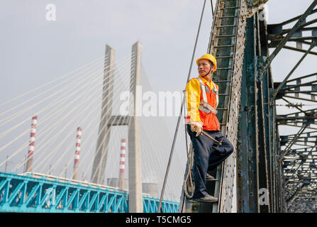 (190423) -- CHONGQING, April 23, 2019 (Xinhua) -- Tang Jinhua looks at the new Baishatuo Yangtze River railway bridge in Jiangjin of southwest China's Chongqing Municipality, April 23, 2019. The previous Baishatuo Yangtze River railway bridge, completed in 1959, will stop service after April 24. All trains will run on the new double decker steel truss cable stay railway bridge after that day. The new bridge has 4 tracks on the upper deck for passenger trains with a designed speed of 200 kilometers per hour and 2 tracks on the lower deck for cargo trains with the designed speed of 120 kilometer - Stock Image