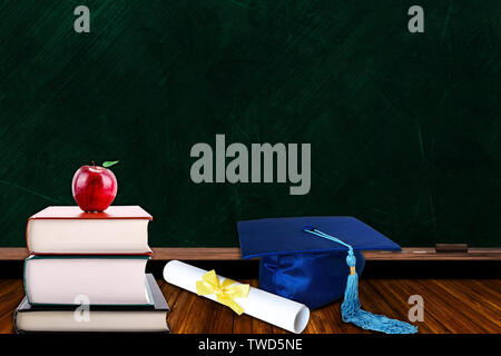 Education concept with blue graduation hat and diploma and stack of books with apple on blackboard background. Copy space on chalk board. - Stock Image