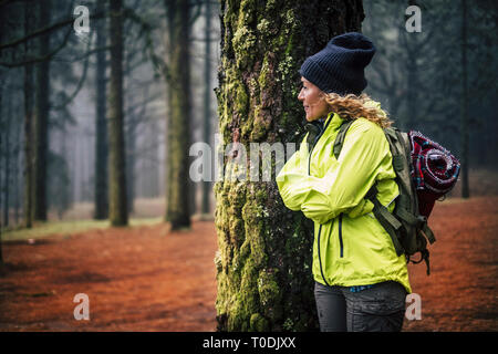 Lonely caucasian middle age woman standing in the forest and look the beautiful wood around her - concept of alternative trekking vacation in wild out - Stock Image