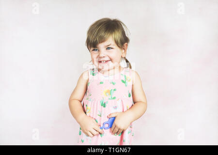 Young little and funny girl in a studio shot - Stock Image