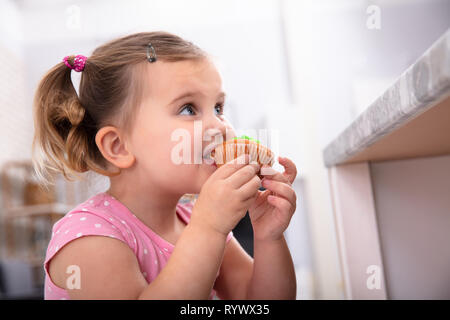 Cute Hungry Girl Taking A Bite Of Delicious Cupcake In The Kitchen - Stock Image