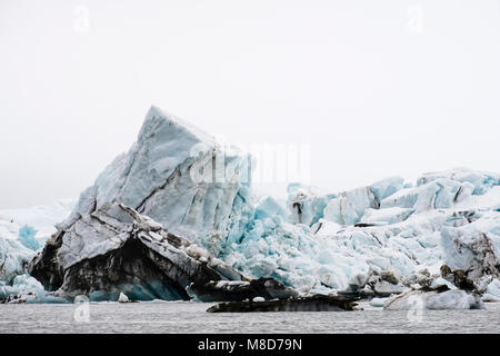 Close view of a dirty terminus of a glacier carving in to the sea in summer 2017. Spitsbergen island, Svalbard, - Stock Image
