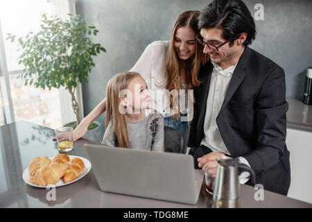 Happy little girl watching a movie on the computer with her father and mother - Stock Image