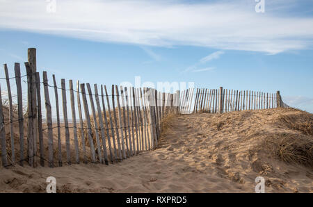 Sand dune with footprints, grass and fence at St Annes on Sea Fylde Coast February 2019 - Stock Image