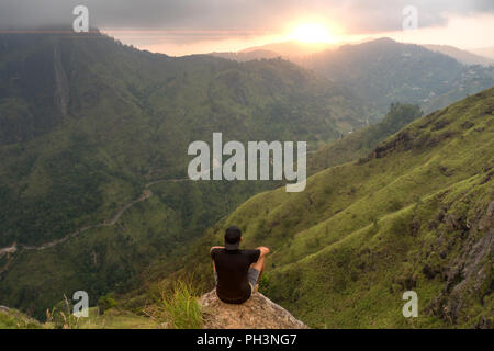 Man sitting on the top of Small Adams peak watching sunset. Ella, Sri Lanka - Stock Image