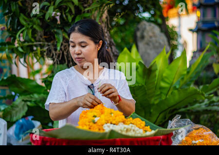 BANGKOK, THAILAND - NOVEMBER 2018: Woman florist arranges orange flowers at the Buddhist temple of Wat Pho in Bangkok, Thailand - Stock Image
