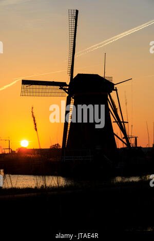 Silhouette of typical windmill framed by the fiery sky at sunset, Kinderdijk, UNESCO, Molenwaard, South Holland, The Netherlands - Stock Image