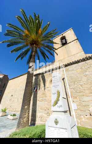In the village of Grimaud, Var, South of France, the church of Saint Michel with the war memorial and palm tree. - Stock Image