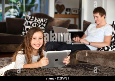 Young girl at home using iPad - Stock Image
