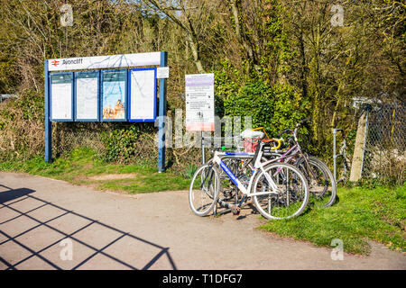 An entrance to Avoncliff railway station with a notice board and several bicycles secured to a metal railing - Stock Image