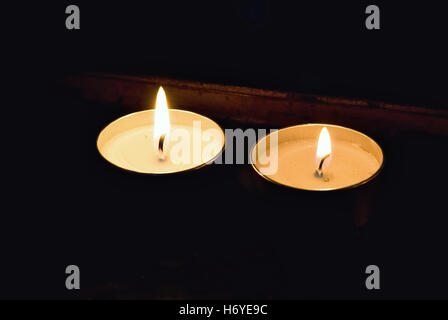 small candle isolated on black background into the church - Stock Image