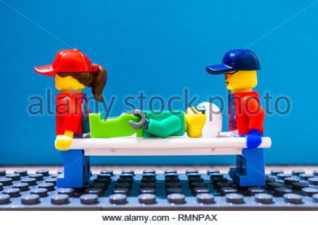 Poznan, Poland - February 12, 2019: Two Lego medical helpers carrying a patient on a bed after a accident. - Stock Image