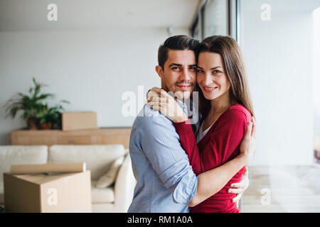 Young couple with cardboard boxes moving in a new home, hugging. - Stock Image