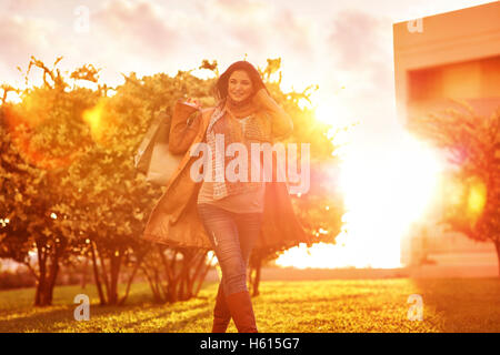 Cheerful pregnant woman with shopping bags in the garden in bright sunny day, autumn season sale, doing purchase - Stock Image