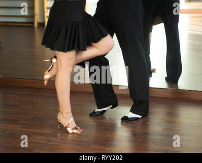 Ballroom dance salsa dancer instructors man and woman couple dancing in shcool rehearsal room - Stock Image