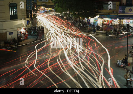 Chaotic traffic is illustrated by the streaking lights in this time exposure of a busy intersection in the Old Quarter, Hanoi, - Stock Image