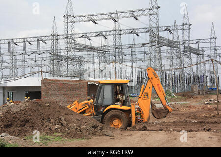 Construction workers busy digging a site for the extension of a powerplant in India. - Stock Image
