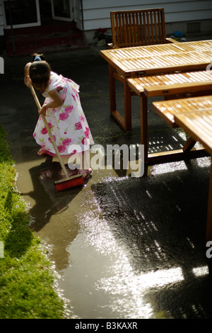 Sweeping away the water Girl aged five with broom - Stock Image