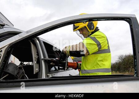 Firefighter cutting the roof off a car at the scene of an accident demonstration, UK. 'Car crash' scene, - Stock Image