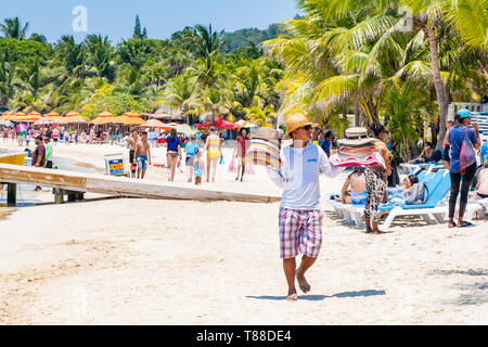 Local male vendor sells hasts to tourists on West Bay Beach Roatan Honduras. - Stock Image