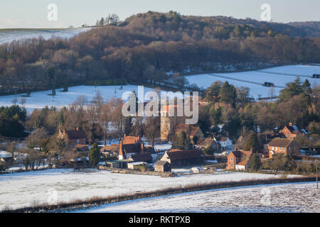 A winter view over the Chiltern village of Fingest with snow on the ground and Cobstone Windmill  on the hill above. - Stock Image