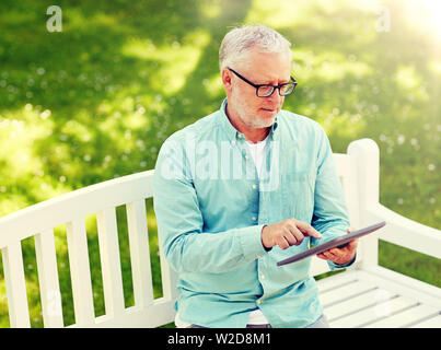 senior man with tablet pc at summer park - Stock Image