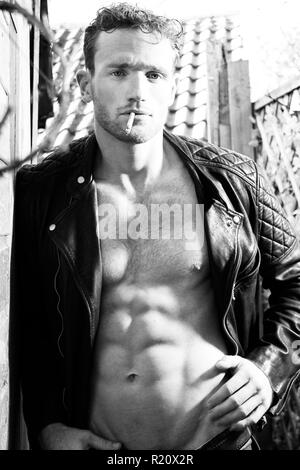 Good looking man with sixpack abs and leather jacket smoking a cigarette and looking at camera - Stock Image