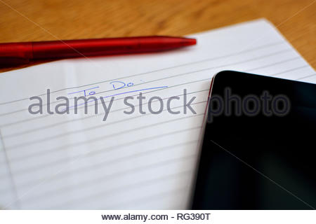 Closeup of lined paper with 'planning' written on the top. Red pen and black tablet / phone also in shot. Planning and organisation with lists looking - Stock Image