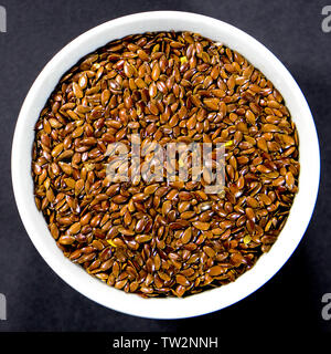 Bowl of Healthy Eating Brown Linseed Seeds High in Fibre and Protein - Stock Image