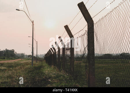 Perimeter fence, chain-link fencing showing the diamond patterning, with barbed wire protecting a property. Vintage toned - Stock Image