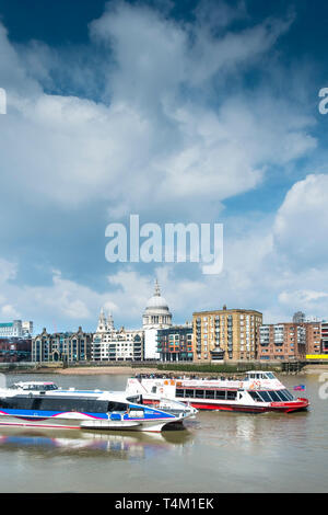 A Thames Clipper River Boat and a City Cruises sightseeing boat on the River Thames with the dome of St Pauls Cathedral in the background. - Stock Image