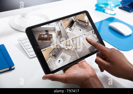 Close-up Of Person's Hand Monitoring CCTV Footage On Digital Tablet - Stock Image