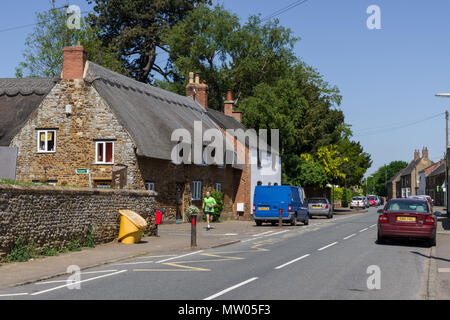 The main street through the village of Little Harrowden, with a fine thatched property to the left plus a lone jogger; Northamptonshire, UK - Stock Image