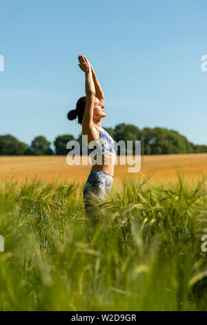 woman practicing yoga and meditation in the sun - Stock Image