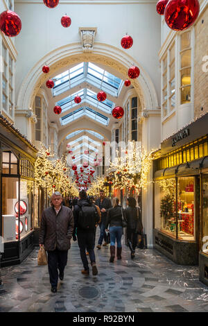 Shoppers walking through Burlington Arcade, a historic (1819) upmarket shopping arcade in Mayfair, central London, England, UK. The arcade is decorate - Stock Image
