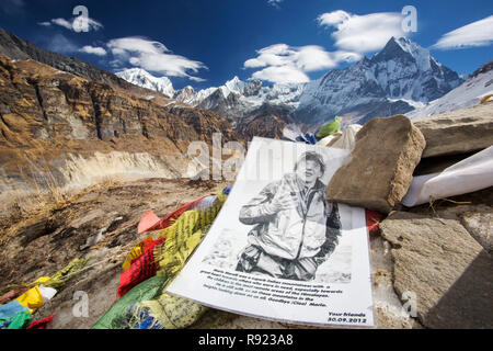 Picture under stones in memorial of climber killed in Annapurna Himalayas, Nepal - Stock Image