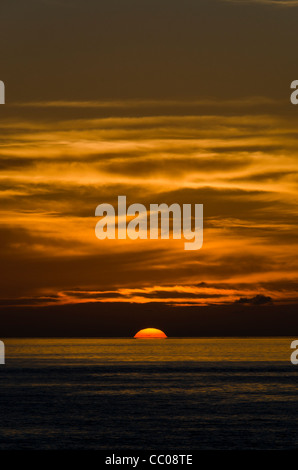 A beautiful golden sunset just before the sun disappeares below the horizon. The light clouds above catch the sun's - Stock Image