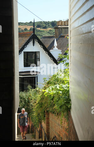 Hastings, UK -July 14 2018: A man seen walking  through a narrow walkway in the Old Town in the fishing port of Hastings on a hot summers day as the temperatures sore to above 27 degrees on 14 July 2018.  Hastings on the south coast of England is 53 miles south-east of London and is 8 miles from where the  Battle of Hastings took place in October 1066. Credit: David Mbiyu Credit: david mbiyu/Alamy Live News - Stock Image