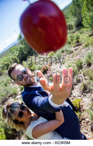 Newlyweds dressed elegantly try to catch a red apple like Adam and Eve. - Stock Image