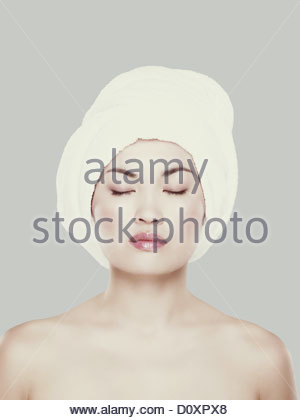 Young woman with hair wrapped in towel - Stock Image