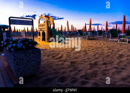 Slide for children on the beach with sunbeds in the background at sunrise time. Jesolo beach, Italy. - Stock Image
