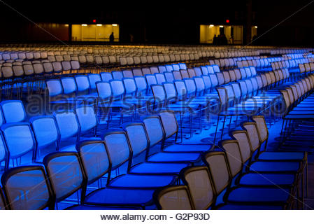 Chairs set up for a business conference in auditorium at night with colored lights side view shallow depth of field - Stock Image