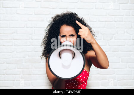 Portrait of angry african american woman shouting with megaphone for protest. Black girl showing rage, anger and rebellion for human rights, strike, p - Stock Image